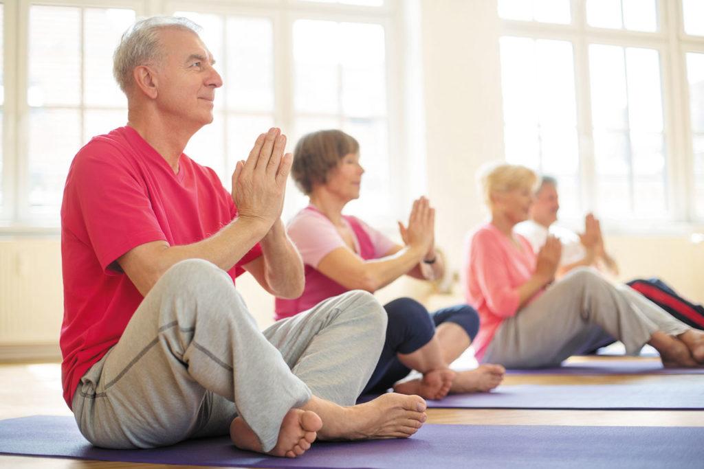 Senior people meditating in yoga class